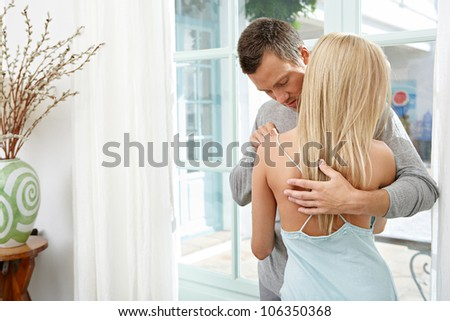 Sexy couple hugging and kissing at home. - stock photo