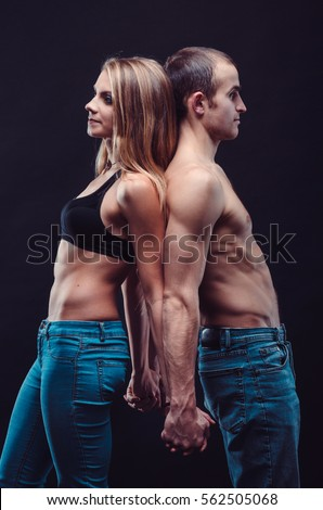 Sexy couple in jeans. Boyfriend and girlfriend embracing in the dark.