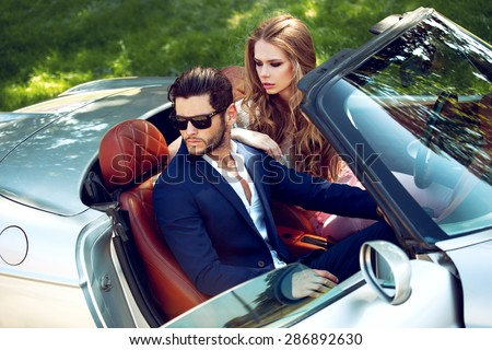 Sexy couple in the car. Luxury life. - stock photo