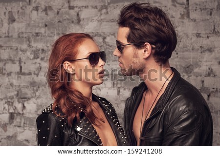 Sexy couple looking at each other through sun glasses. Romantic moment  - stock photo
