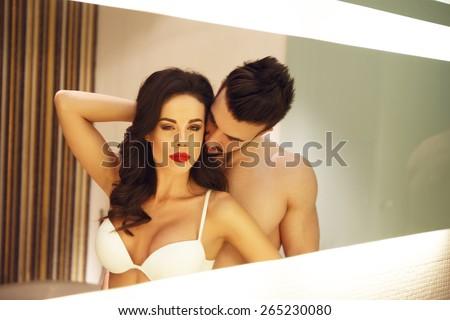 Sexy couple posing in bathroom mirror - stock photo