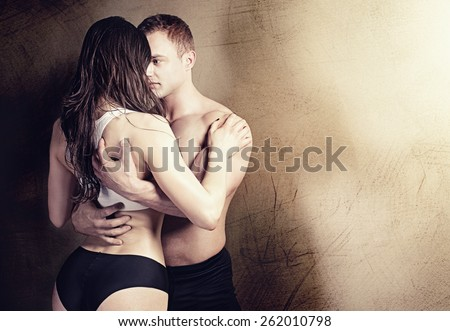 Sexy couple posing in  studio. Handsome muscular man with girlfriend. - stock photo