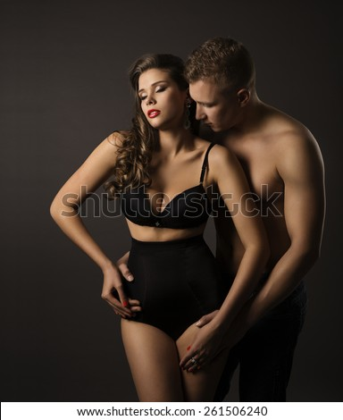 Sexy Couple Woman and Man Portrait, Female in Sensual High Waist Underwear Panties, Kissing Boyfriend over Black Background - stock photo