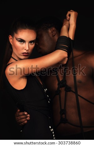 Sexy couple; woman in a black swimsuit handmade with her man, girl hands tied with rope