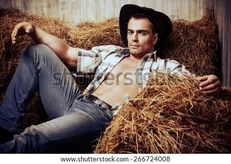 Sexy cowboy lying on a haystack. Western style. Jeans denim fashion. - stock photo