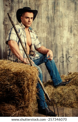 Sexy cowboy on a haystack. Western style. - stock photo