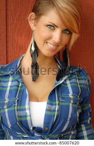 Sexy Cowgirl against red barn wearing Feather Earrings - stock photo