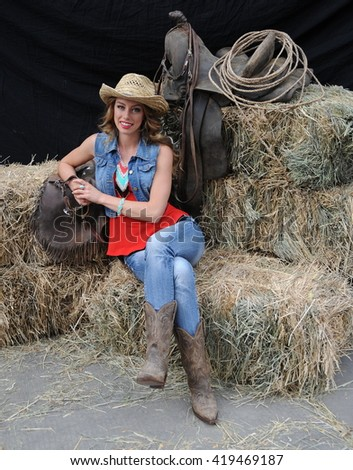 Sexy cowgirl sitting on haystacks outdoors.