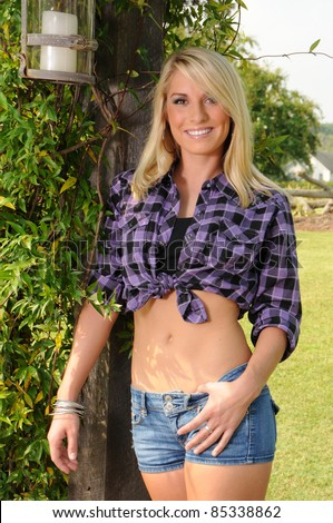 Sexy Cowgirl wearing a Plaid Shirt and Jean Shorts - stock photo