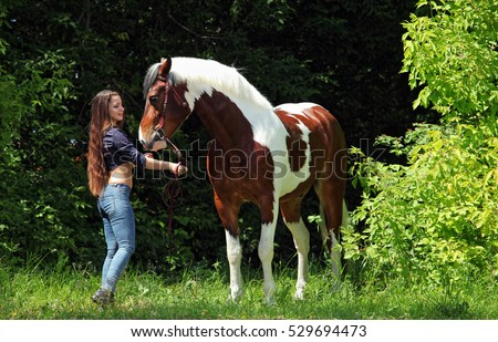 Sexy cowgirl with her horse in green forest