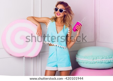 Sexy cute curly blonde girl in sunglasses with beautiful skin and lips, posing in studio, drinking fruit juice or cocktail. Wearing vintage heart sunglasses, stylish blue leather top.
