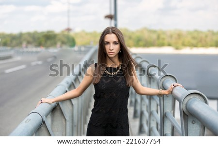 Sexy dark haired woman in black dress posing on urban bridge