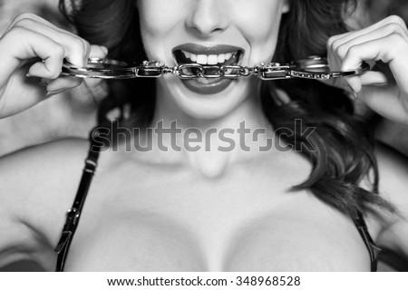 Sexy dominatrix bite handcuffs, black and white, bdsm - stock photo