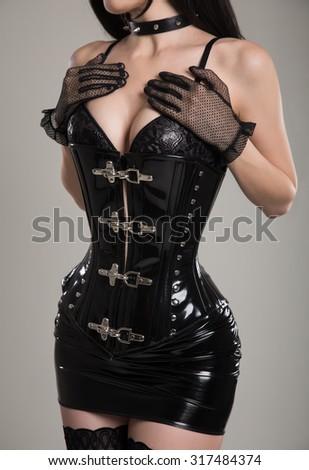 Sexy dominatrix woman in black fetish corset and mini skirt, studio shot  - stock photo
