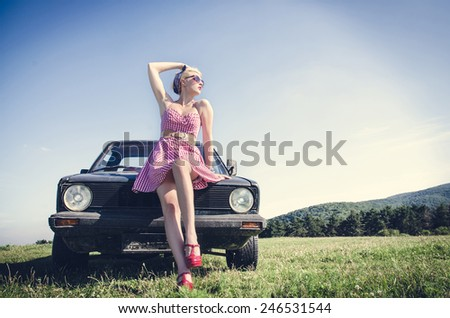 Sexy dressed vintage female model posing next to retro car on a field - stock photo