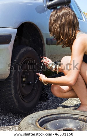 Sexy dressed woman tightening the wheel nuts after changing a flat tire for a spare - stock photo