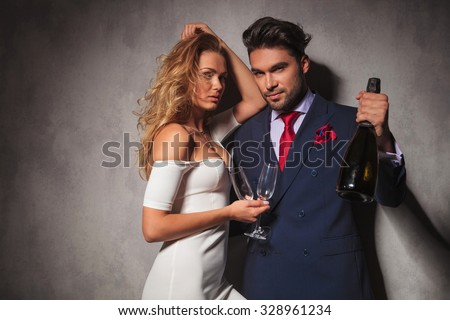 sexy elegant couple with bottle of champagne , posing in studio - stock photo