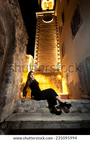 Sexy elegant woman sitting on stone bench on old street - stock photo