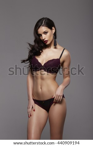 Sexy fashion brunette woman with long dark hair and red lips in vinous  lace lingerie and black earrings  - stock photo