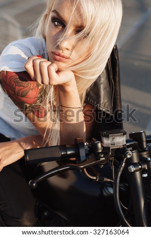Sexy fashion female biker. Close-up of Woman sitting on vintage custom motorcycle. Outdoor lifestyle portrait - stock photo