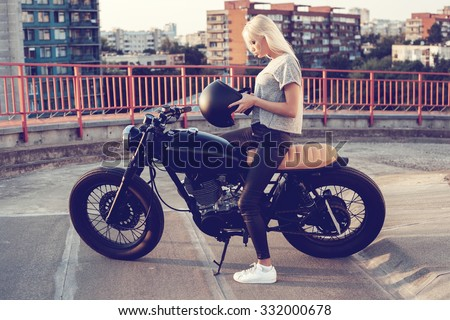 Sexy fashion female biker girl. Young Blonde woman  sitting on vintage custom motorbike. Outdoors lifestyle toned portrait