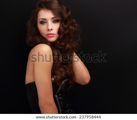 Sexy fashion female model in modern black dress posing on black background - stock photo