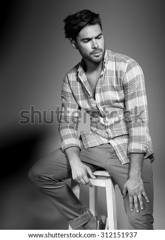 sexy fashion male model dressed casual posing against wall