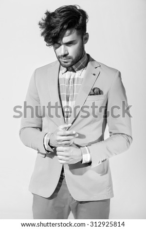 sexy fashion male model dressed elegant - casual posing against wall - stock photo