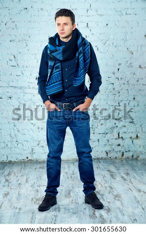 Sexy fashion man dressed casual brick blue wall. Modern fashion style man. Fashion man standing near a brick blue wall. - stock photo
