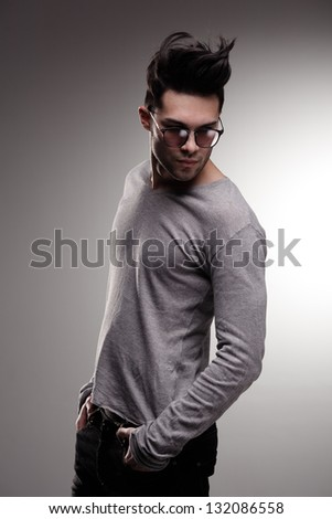 sexy fashion man model dressed casual posing dramatic in the studio - low key - stock photo