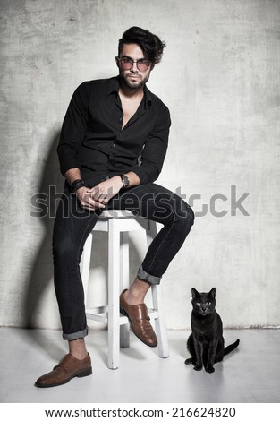 sexy fashion man model dressed casual posing with a cat against grunge wall - stock photo