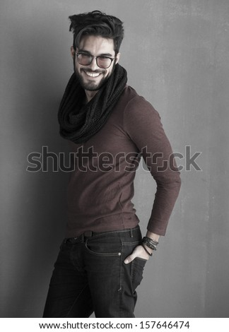 sexy fashion man model dressed casual smiling against wall