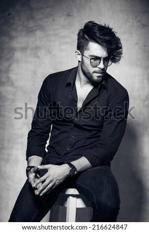 sexy fashion man model dressed casual wearing glasses posing dramatic against grunge wall