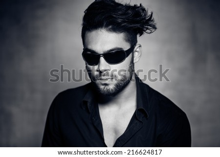 sexy fashion man model dressed casual wearing sun glasses posing dramatic