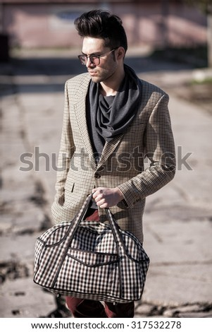 sexy fashion man model dressed vintage elegant holding a bag posing outdoor