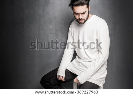sexy fashion man model in white blouse, jeans and boots posing dramatic against wall