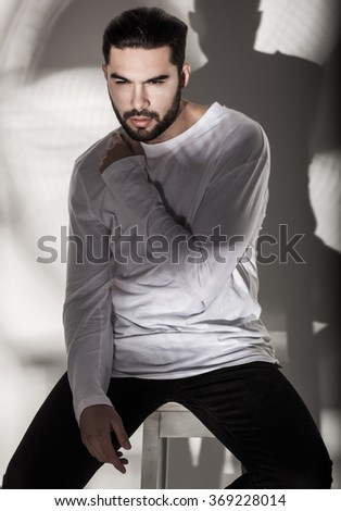 sexy fashion man model in white blouse, jeans and boots posing dramatic against wall - stock photo