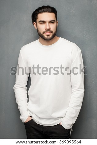 sexy fashion man model in white sweater, jeans and boots posing dramatic - stock photo