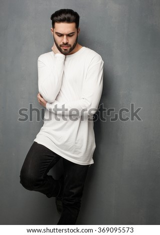 sexy fashion man model in white sweater, jeans and boots posing dramatic