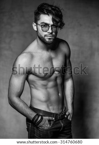 sexy fashion man model top naked posing dramatic against grunge wall