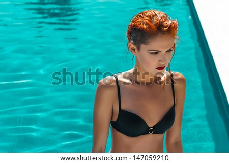 Sexy fashion model posing in the pool, high fashion - stock photo