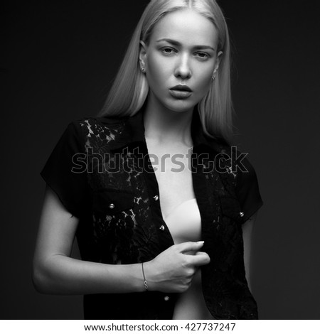 sexy fashion model with long hair, perfect skin is posing in studio for glamour vogue test photo shoot showing different poses. Picture taken in the studio on a gray background. Black and white photo