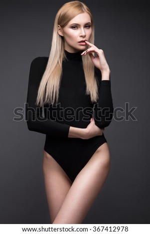 sexy fashion model with long hair, young European attractive, beautiful eyes, perfect skin is posing in studio for glamour vogue test photo shoot showing different poses. Picture taken in the studio