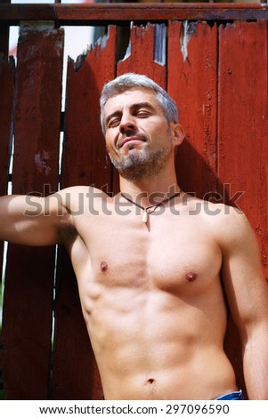 Sexy fashion portrait hot male model with muscular body posing. Wolves tooth jewelery pendant. - stock photo