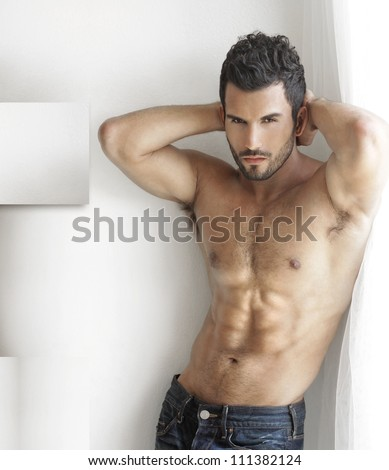 Sexy fashion portrait of a hot male model in stylish jeans with muscular body posing in modern interior setting with window light