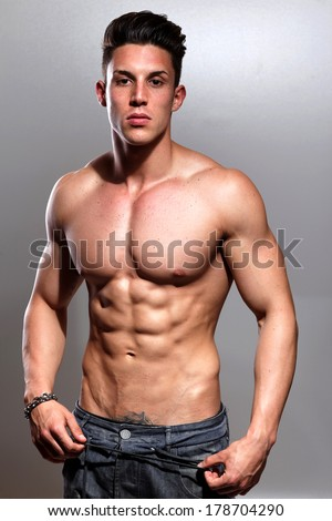 Sexy fashion portrait of a hot male model in stylish jeans with muscular body posing in studio.Glamour colors - stock photo
