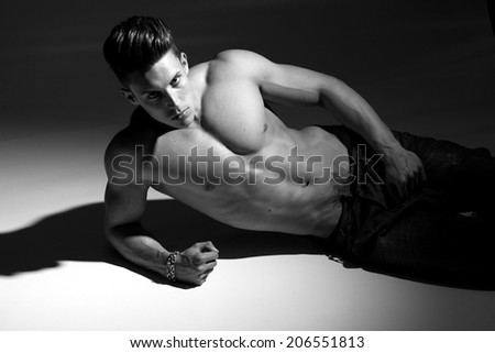 Sexy fashion portrait of a hot male model in stylish jeans with muscular body posing in studio.Glamour photo. B&W.