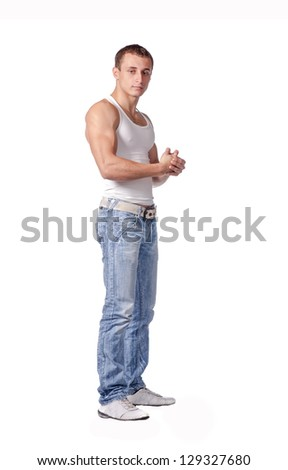 Sexy fashion portrait of a hot male model in stylish jeans with muscular body posing in studio on white - stock photo