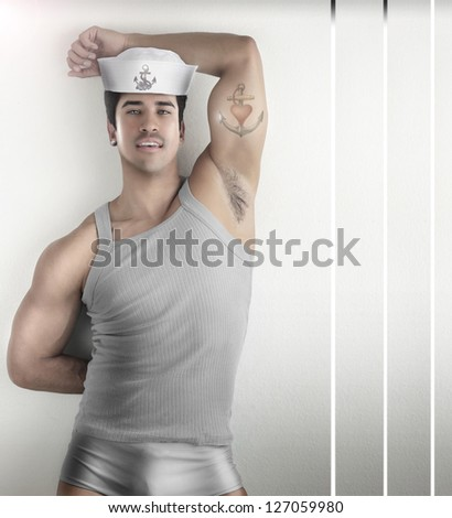 Sexy fashion portrait of a male model in provocative sailor outfit against modern futuristic background - stock photo