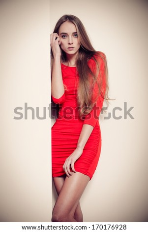 Sexy fashion woman in red dress posing near the wall - stock photo